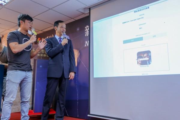 新北市長朱立倫(右)透過BizWitcher收併購平台拍賣自拍照,體驗區塊鏈技術應用。(新北市政府經濟發展局提供)