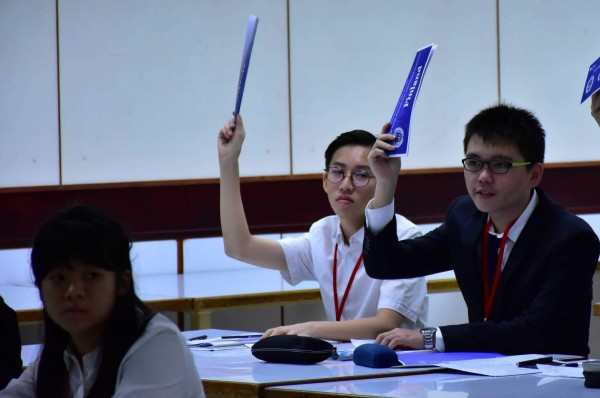 明道中學舉辦跨校性「模擬聯合國會議」,參與學生舉手發言,全程並以英文模擬聯合國會議的發言。(記者陳建志翻攝)
