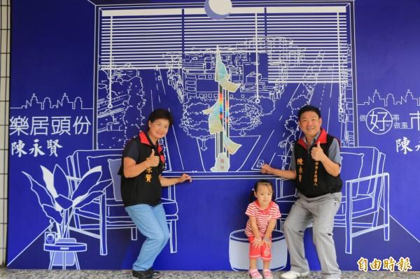 頭份市長參選人陳永賢(右)與妻子(左)帶著小孫女(中)在頭份「藍晒圖」前合影。(記者鄭名翔攝)