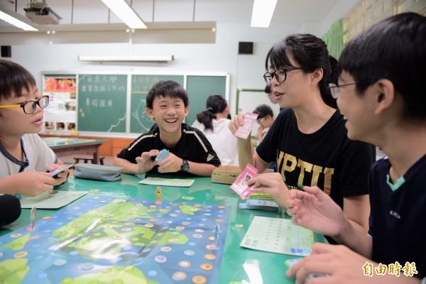 屏東大學學生與屏大附設實驗小學一起玩桌遊。(記者邱芷柔攝)