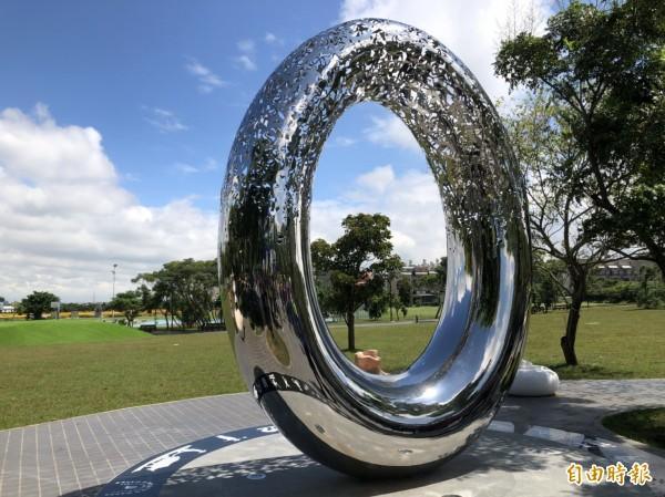 藝術家姜憲明的「健康之環」以不鏽鋼打造「0」外型,上頭鏤刻跑步、足球、棒球等運動類型,象徵生命最重要的健康。(記者許倬勛攝)