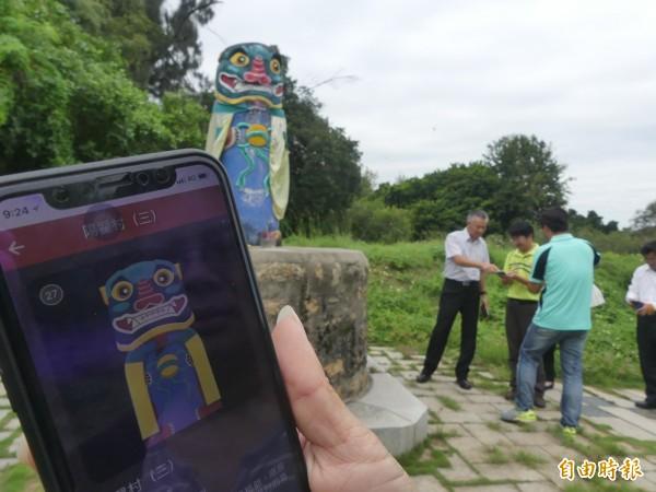 遊客用手機下載「金沙鎮巡禮之尋找風獅爺」App,就可以在金門抓「寶」。(記者吳正庭攝)