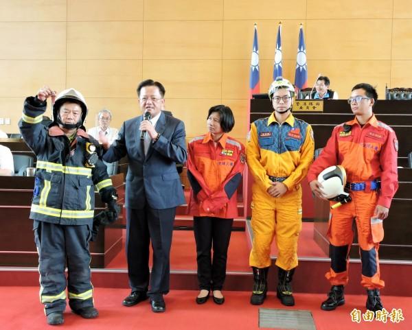 市議員鄭功進(左1)穿上消防衣,並請副市長林依瑩換上(左3)的救助服,由消防局長蕭煥章(左2)說明兩者的用途。(記者張菁雅攝)