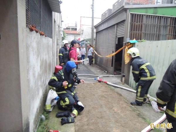 苗栗市民宅發生火警,因位在窄巷內,消防人員引水灌救。(記者張勳騰攝)