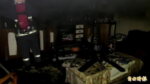 消防人員進入客廳灌救。(記者張勳騰攝)