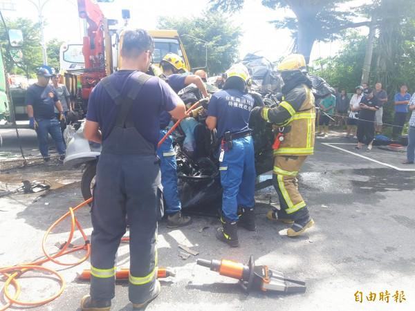 消防人員合力搶救受困自小客駕駛。(記者陳賢義攝)