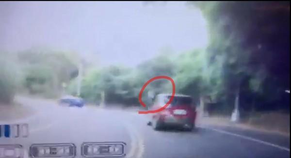 紅色轎車駕駛丟出面紙團,白色物飛在空中。(圖擷自林姓民眾影片)