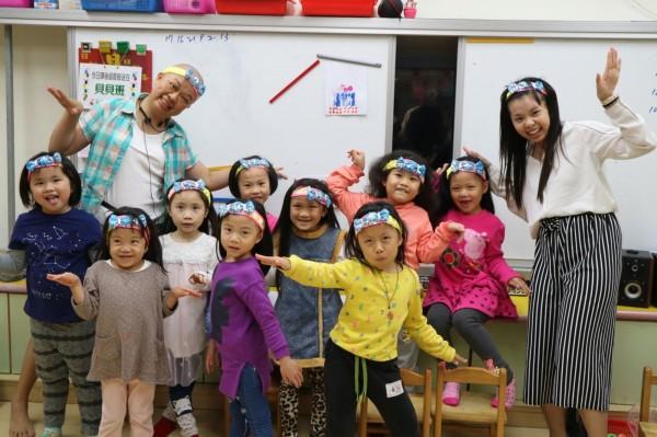 林淑綾化療後頭髮掉光(後排左),有時候會脫下假髮,趁機為孩子們上一堂生命課程。(新北市教育局提供)