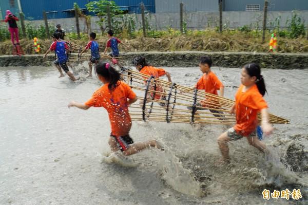 濁溪搶水文化節登場,小朋友4人一組扛著「籠仔笱」,在水深約30公分的泥巴水中競速賽跑。(記者詹士弘攝)