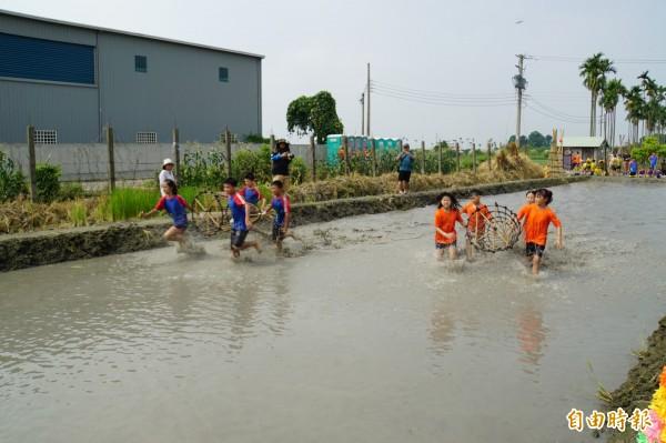 小朋友「搶水」初體驗,扛著「籠仔笱」在泥巴水競速。(記者詹士弘攝)