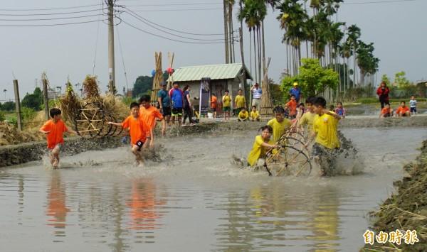 泥巴水中考驗「搶水」技術,一不小心就跌進水中。(記者詹士弘攝)