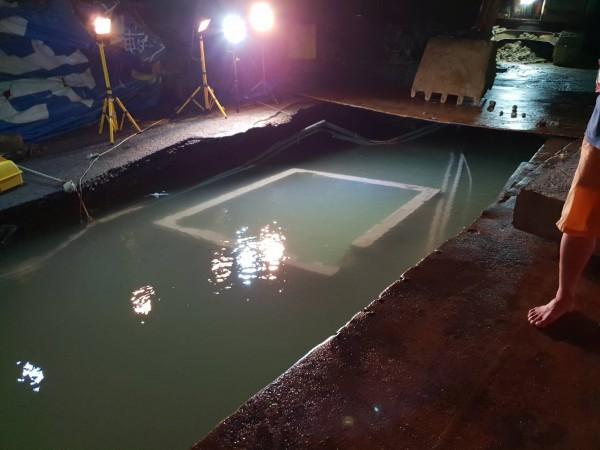 基隆調和街觀海街口自來水管破管,現在出現一個大洞,水公司人員現場查勘評估何時可修復。(讀者提供)