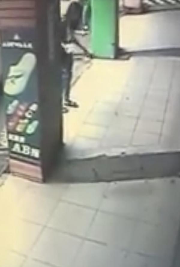 情侶遛狗皮夾從口袋滑出,圖中長髮女子撿起又覺不妥放回原地。(翻攝臉書「爆料公社」)