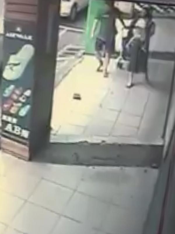 情侶遛狗皮夾從口袋滑出,圖中推著嬰兒車的夫妻當孩子的面撿走。(翻攝臉書「爆料公社」)