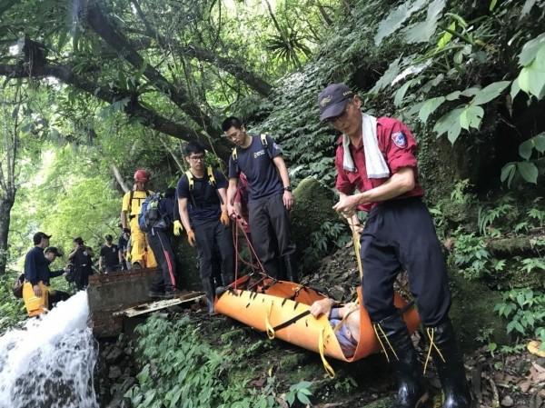消防隊員將受傷的黃姓老翁吊掛下山。(記者鄭名翔翻攝)