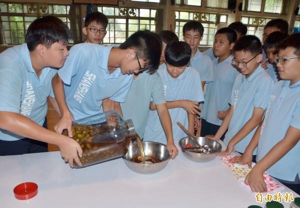 橄欖醋開封後,學子們小心地倒出來。(記者吳俊鋒攝)