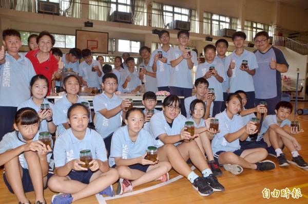 分裝後,學子們開心展示守護了9個月的橄欖醋。(記者吳俊鋒攝)