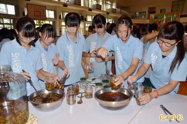 學生將甕裡倒出來的橄欖醋,分裝在小罐子。(記者吳俊鋒攝)