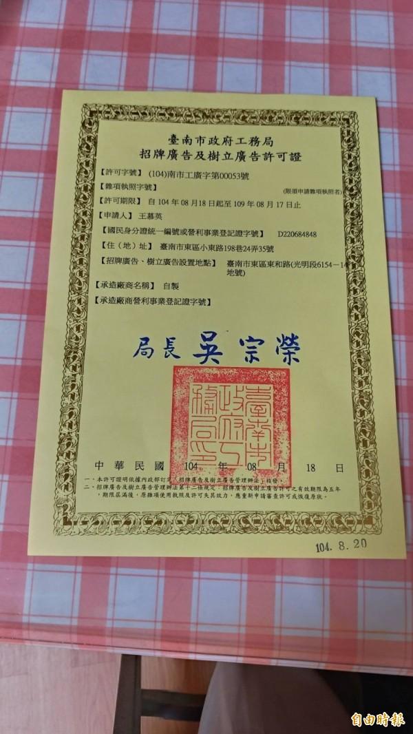 王慕英出示她向市府工務局申請獲准的廣告物樹立許可證。(記者王俊忠攝)