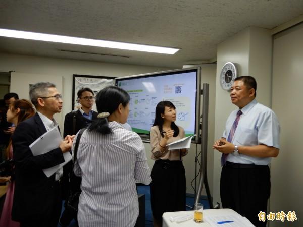 日本記者圍著台東地區農會總幹事李建通詢問冷凍釋迦的銷日細節。(記者林翠儀攝)