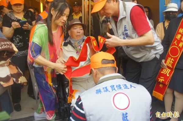 中風的藍俊逸議員,為愛子披掛綵帶代父出征今年議員選戰。(記者劉禹慶攝)