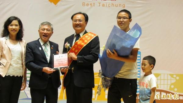 林志隆(中)獲好人好事代表,遭酒駕重創、奇蹟康復出院的王俊昇(右)上台獻花見證。(記者蘇孟娟攝)