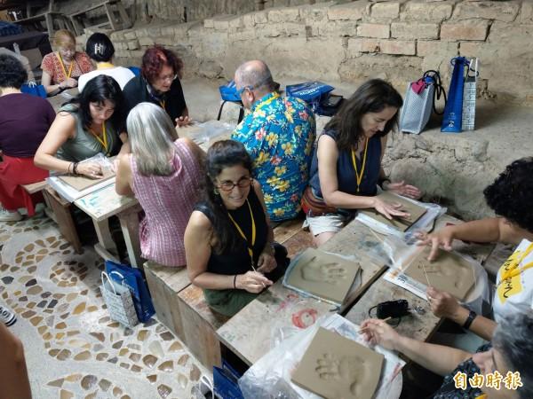 聯合國教科文組織的國際陶藝學會成員前往水里蛇窯參訪,並在陶土板上留下手印,作為台灣與國際交流的見證。(記者劉濱銓攝)