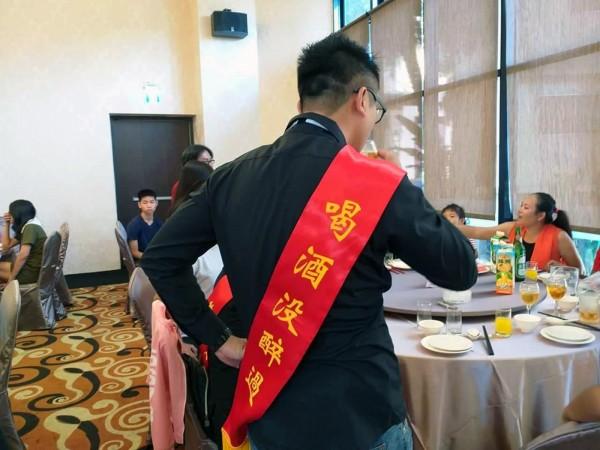 94狂!草屯鎮一場婚宴中,當「擋酒司令官」的李韋彤所披的綵帶,背面寫「喝酒沒醉過」。(陳國大提供)