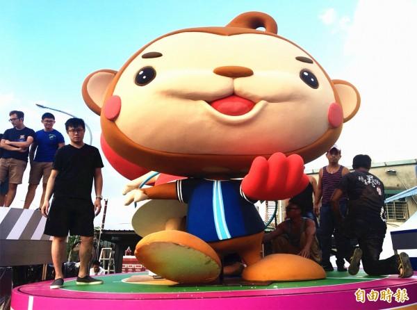 桃園市吉祥物ㄚ桃、園哥將站在花車中間轉盤上,因高達5公尺,正進行組裝作業的最後調整。(記者李容萍攝)