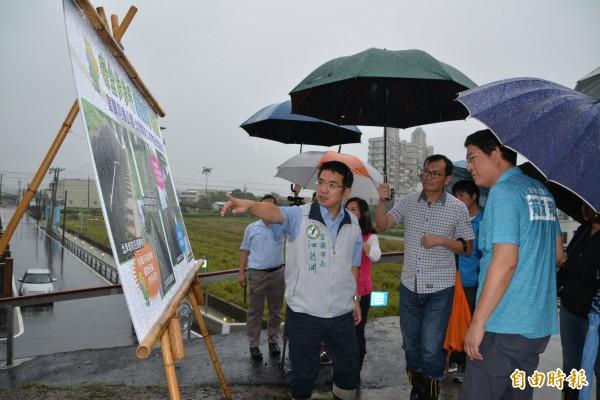 宜蘭市長江聰淵(左)等人,今天冒雨會勘宜蘭河濱公園工作梯扶手設置情形。(記者游明金攝)