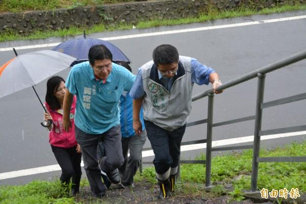 宜蘭市長江聰淵(右)等人,今天冒雨會勘宜蘭河濱公園工作梯扶手設置情形。(記者游明金攝)