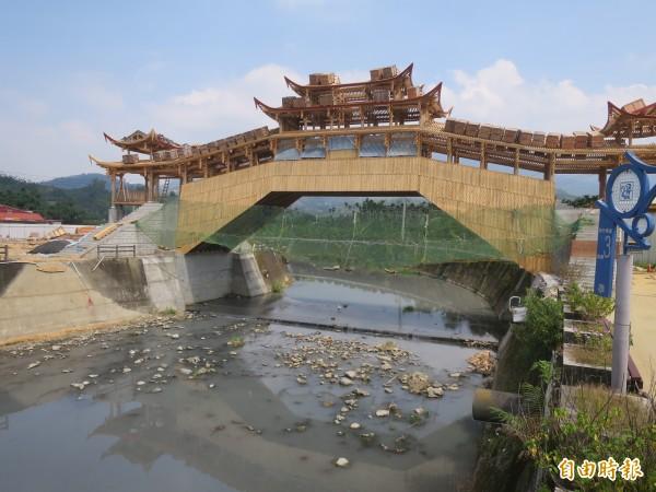 集集鎮武昌宮旁正在興建的中國廊橋即將完工,惟橋下卻是污濁水流,景象形成強烈對比。(記者劉濱銓攝)