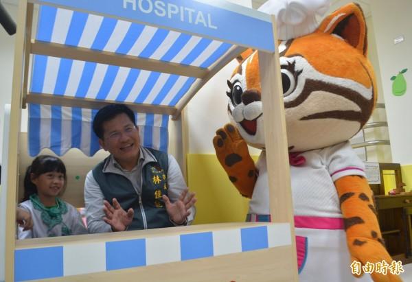 太平坪林親子館暨托嬰中心今天正式開幕,林佳龍市長(右)進館參觀,還扮起病人讓小小醫生看診。(記者陳建志攝)