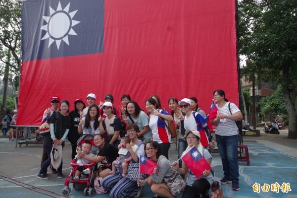 民眾爭相在巨幅國旗前合影,祝國家生日快樂。(記者林國賢攝)