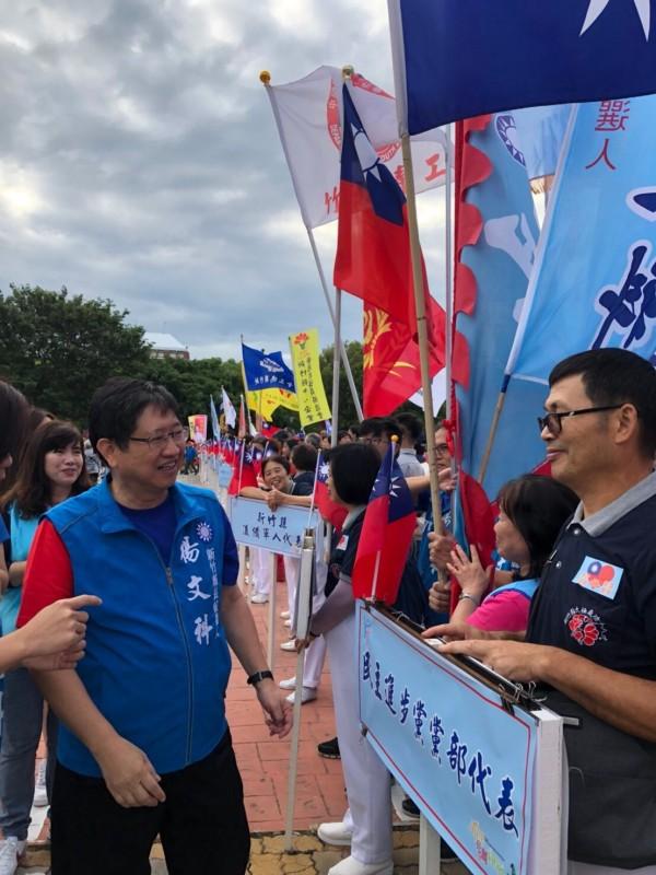 國民黨新竹縣長參選人楊文科今早很早就到府前廣場向參加國慶升旗的民眾問好。(圖由楊文科陣營提供)
