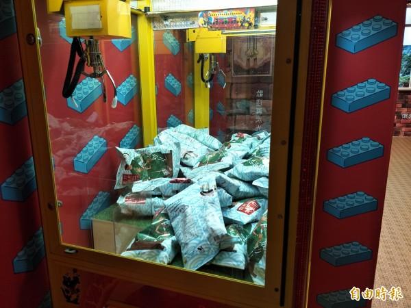 館內遊戲區的夾娃娃機改放洋芋片。(記者邱灝唐攝)