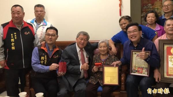 百歲婆馮賴寶妹(坐者右)的家屬「爆料」,百歲婆愛美,出門一定儀容端莊整齊,90幾歲時還在子孫指導下學用遮暇膏。(記者黃美珠攝)