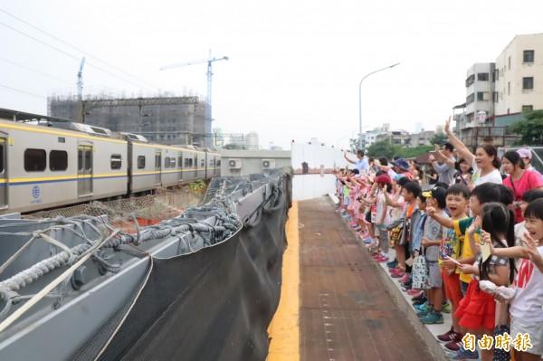 三民國小師生隔著柵欄揮別火車最後身影。(記者方志賢攝)