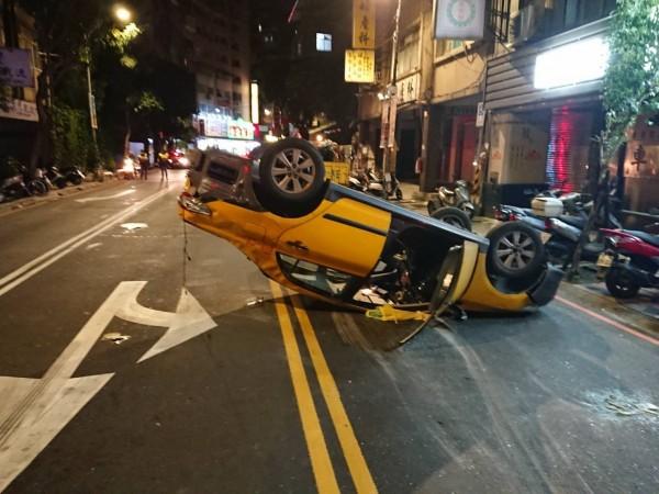 計程車遭撞後,翻滾180度,擋風玻璃全部碎裂在地,駕駛車門噴出。(記者陳薏云翻攝)