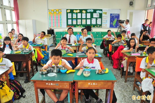 花蓮縣代理縣長蔡碧仲(後排左)和學生共進營養午餐,強調營養午餐決不停辦,且好還要更好。(記者花孟璟攝)