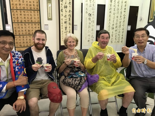 外國遊客品嚐「手揉腳踏」的烏龍麵,一飽口福。(記者林欣漢攝)