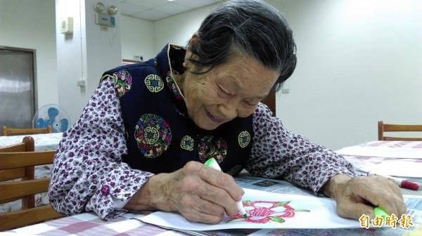 92歲的阿嬤王桂過去沒有拿過畫筆的經驗,如今在創作中獲得快樂。(記者林欣漢攝)