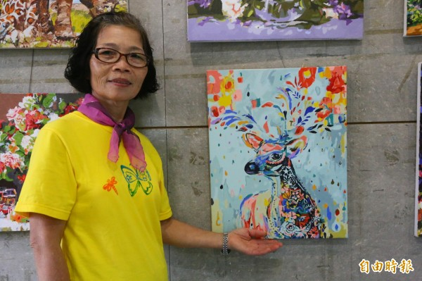 賴阿幼靠著放大鏡一筆筆費時完成創作,色彩繽紛又美麗。(記者林欣漢攝)