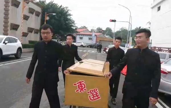 虎尾鎮長候選人陳獻堂今天躺棺材到抽籤現場完成抽籤,抽中4號。(記者黃淑莉翻攝)