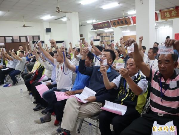 鎮清宮臨時信徒大會,出席信徒拿著會員證舉手表決,通過解除前主委王涼洲一切職務。(記者歐素美攝)