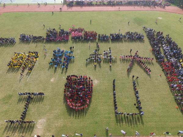 明新科技大學慶祝52歲生日,今天有千名學生在田徑場上排出「明新科大I?U」7個大字,別開生面地為運動會揭開序幕。(明新科大提供)