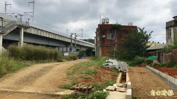 新竹縣高鐵橋下連絡道延伸入竹科的2期工程施工進度已經達八成,但因途中遠方這棟紅色磚造民宅尚未拆遷,道路邊溝也只能做到「最後1哩路」前嘎然暫時停止。(記者黃美珠攝)