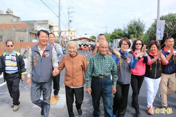 後龍鎮長朱秋隆(左二)與苗栗副縣長鄧桂菊(右三)牽著當地九旬老夫婦,一起踏上新闢的道路。(記者鄭名翔攝)