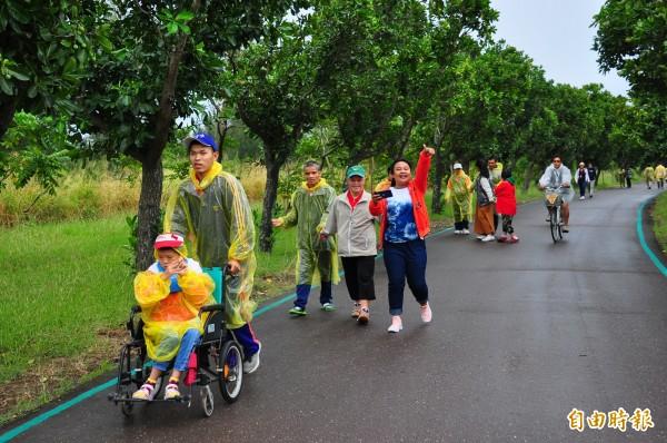 中度障別的學員發揮互助合作精神,協助重度、極重度的學員完成健走。(記者王秀亭攝)