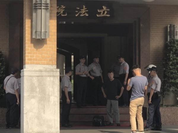 江男(黑衣者)今年八月時曾提油到立法院抗議。(資料照)